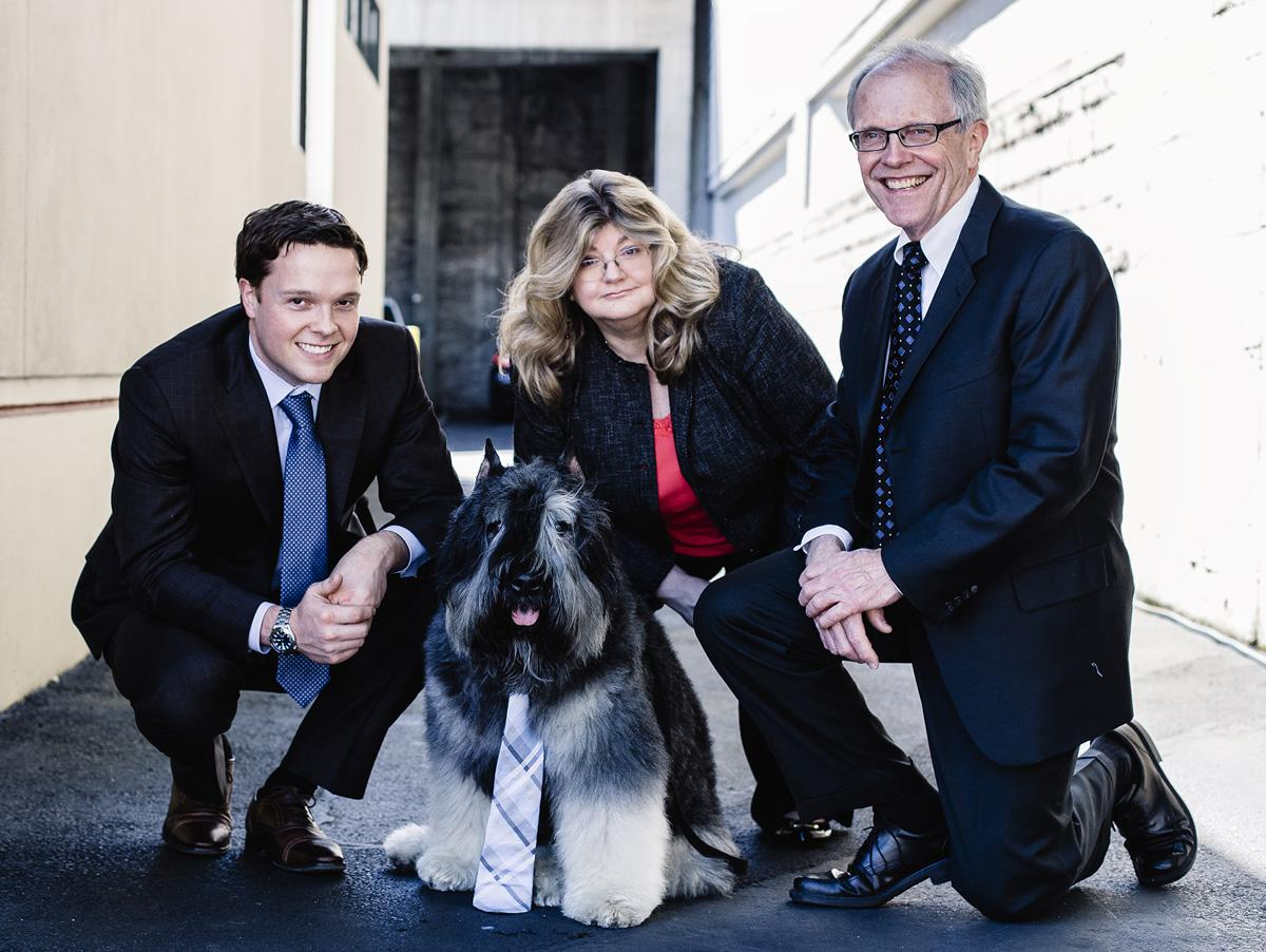 This photo features Helland Law Group's shaggy office dog, Slater, wearing a tie. Crouched around him in business attire are the firm's three attorneys. Tacoma WA is the backdrop for this scene, specifically an alley, but