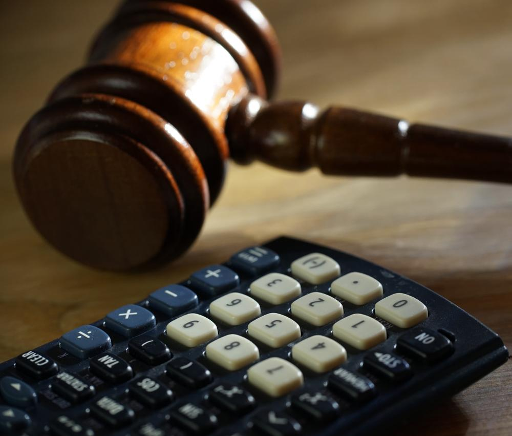 Click to enlarge A lawyer uses a calculator representing the idea of personal injury calculator