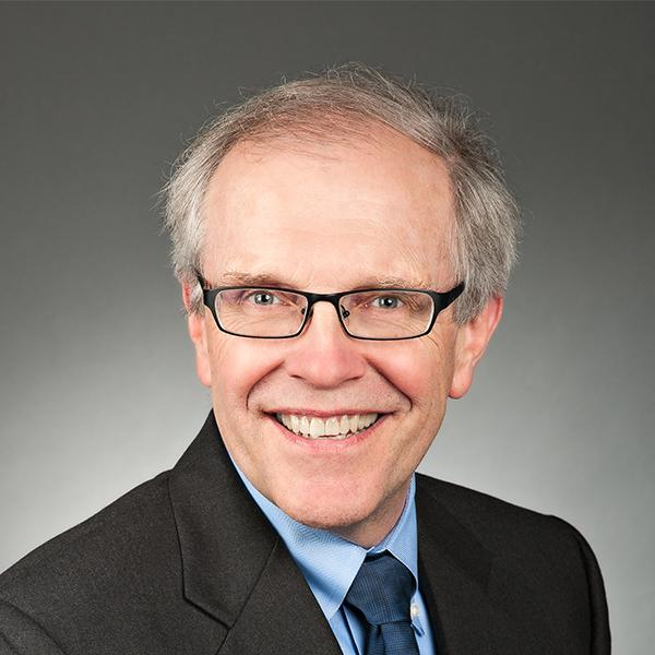 Against a simple smooth background, this photo, which cropped so that it is circular in shape, is a head shot of Attorney Robert Helland. Tacoma, WA-based, Robert Helland has grey hair, a friendly smile, trendy glasses, an